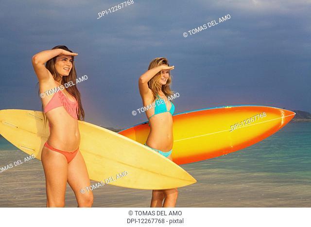 Teenage sisters with their surfboards; Kailua, Island of Hawaii, Hawaii, United States of America