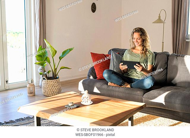 Happy woman realxing on couch at home using tablet