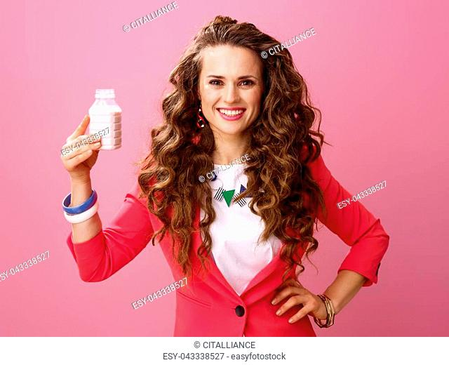 Pink Mood. Portrait of happy young woman with long wavy brunette hair on pink background showing farm organic yogurt