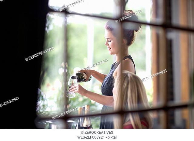 Waitress in restaurant serving red wine