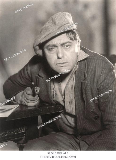 Portrait of despondent man pointing gun