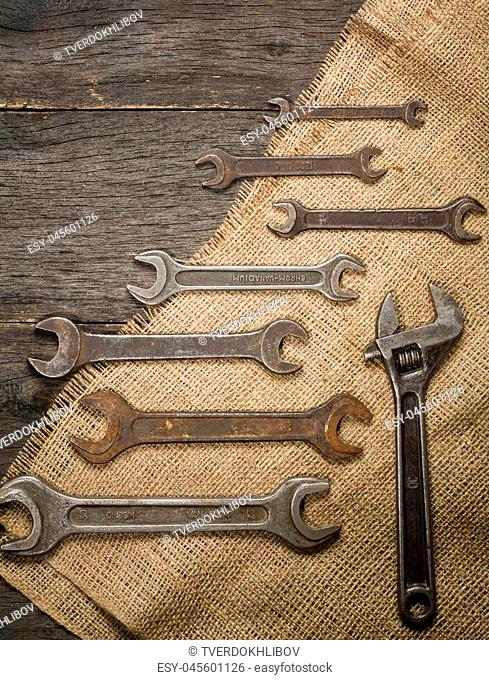 old and rusty spanners on a background of a wooden table and sacking. Space for text