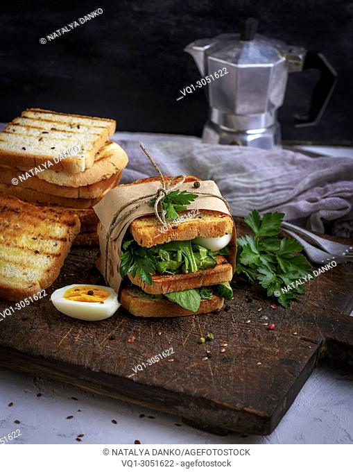 sandwich of French toast and lettuce leaves and boiled egg, a vegetarian food wrapped in paper on a wooden board