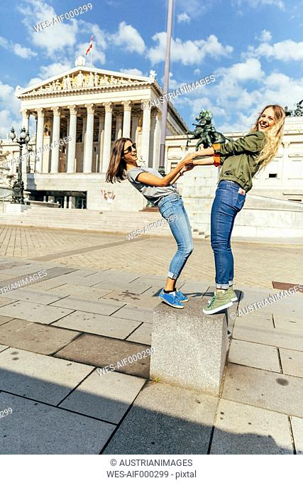 Austria, Vienna, two young women having fun in front of the parliament building