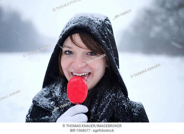 Girl eating ice cream despite low temperatures in winter