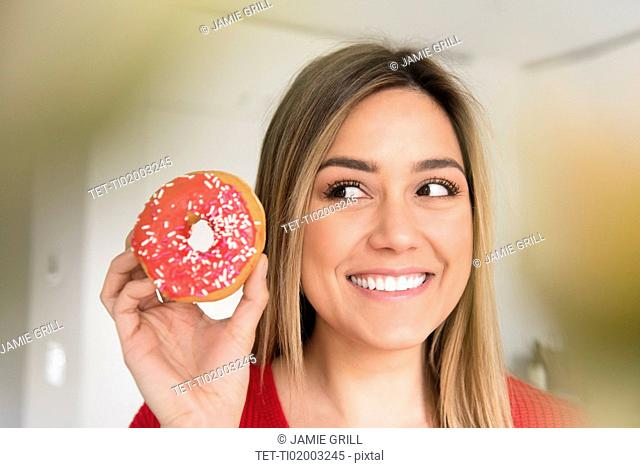 Smiling young woman holding donut with pink icing