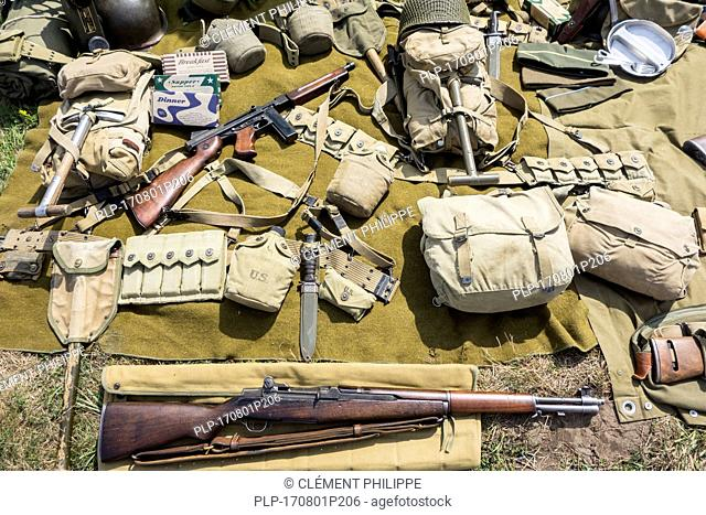 WW2 US soldier outfit and weapons displayed on the ground at World War Two militaria fair showing M1 Garand rifle and Thompson submachine gun