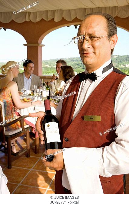 Waiter holding wine bottle with well-dressed couples dining in background