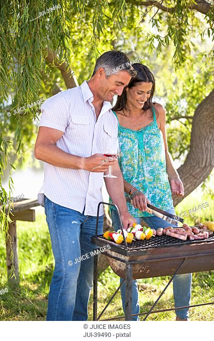 Couple Cooking Barbeque In Countryside