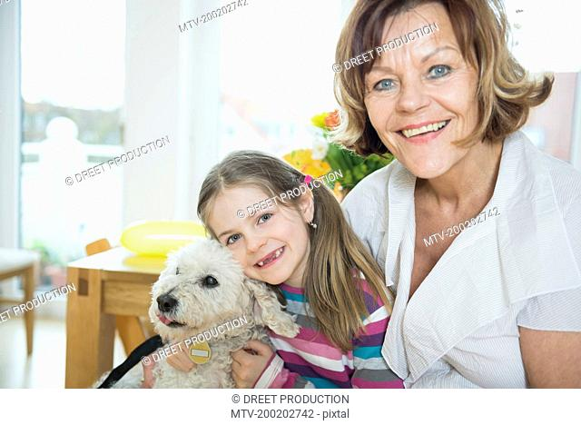 Portrait of grandmother and grandchild with dog in living room, smiling