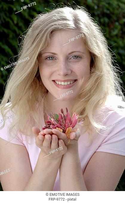 Smiling woman holding honeysuckle