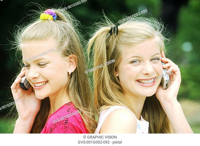 Two girls talking on a mobile phone outdoors