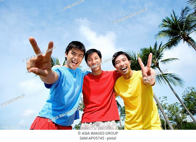 Men with arms around each other, looking at camera, making peace sign