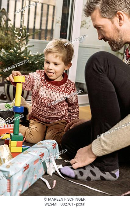 Father and son playing with building bricks in front of Christmas tree