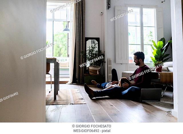 Affectionate couple with laptop relaxing on the floor at home