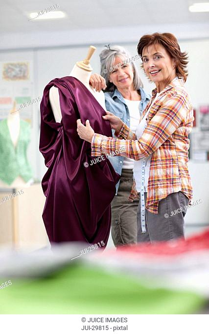 Designers assessing evening gown on dressmakerís dummy in classroom