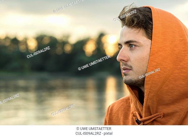 Young man wearing orange hooded top