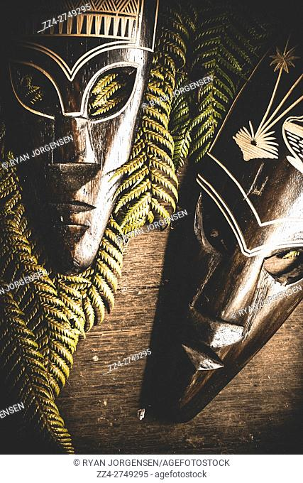 Cultural still life photo on African traditional tribal masks with rainforest ferns on old wood table. Clash of civilisations