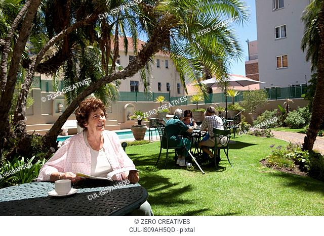Senior woman having coffee in garden of retirement villa