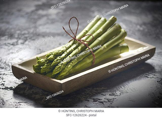 A bundle of green asparagus in a wooden dish