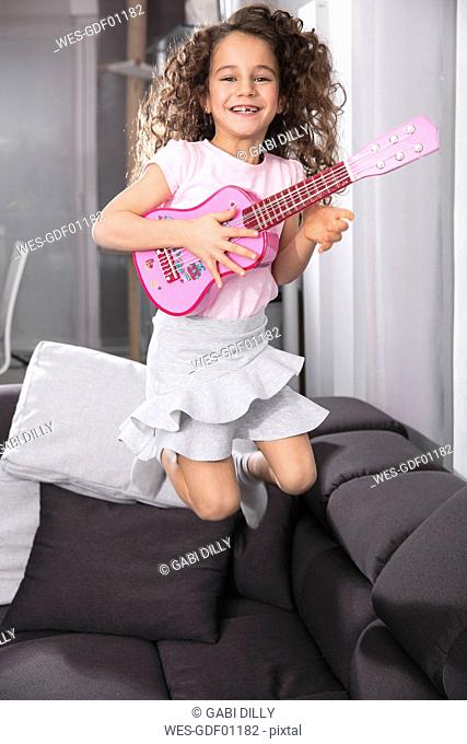 Portrait of happy little girl with pink toy guitar jumping in the air on the couch