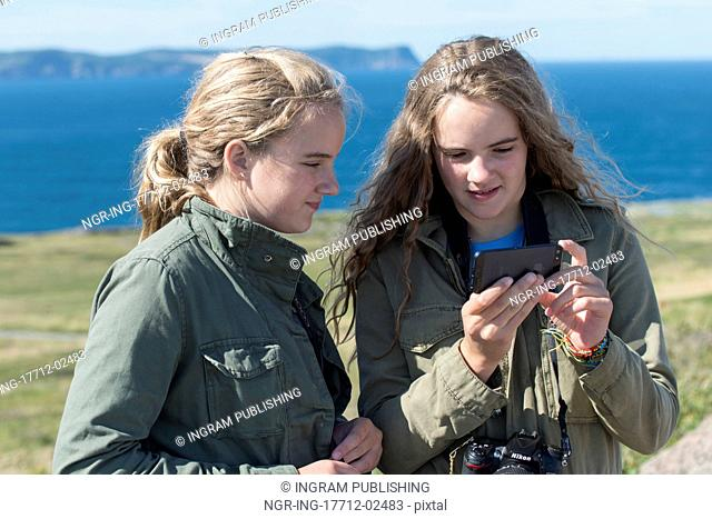 Girls looking at mobile phone on coast, Cape Spear, St. John's, Newfoundland And Labrador, Canada