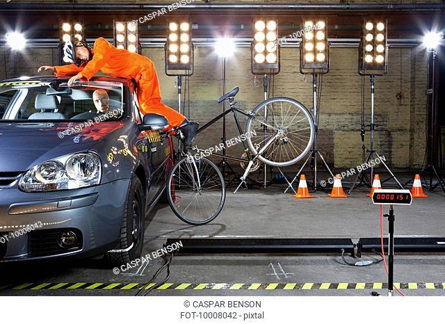 A crash test dummy on a bicycle crashing into a car