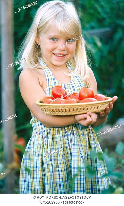 Little girl with a basket of plum tomatoes