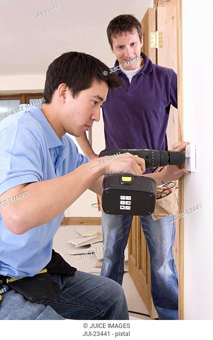 Electrician watching co-worker drill outlet in wall