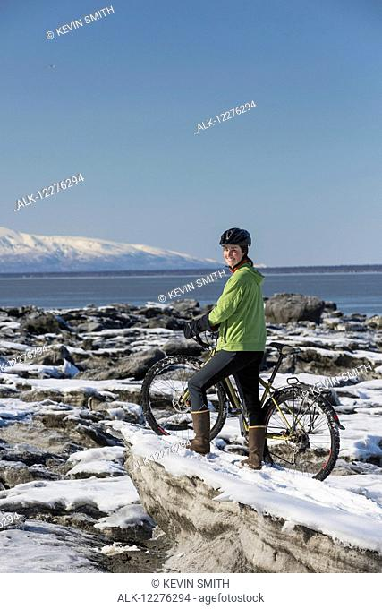 A young woman stands with her bicycle on ice next to the Tony Knowles Coastal Trail, Anchorage, Southcentral Alaska, USA