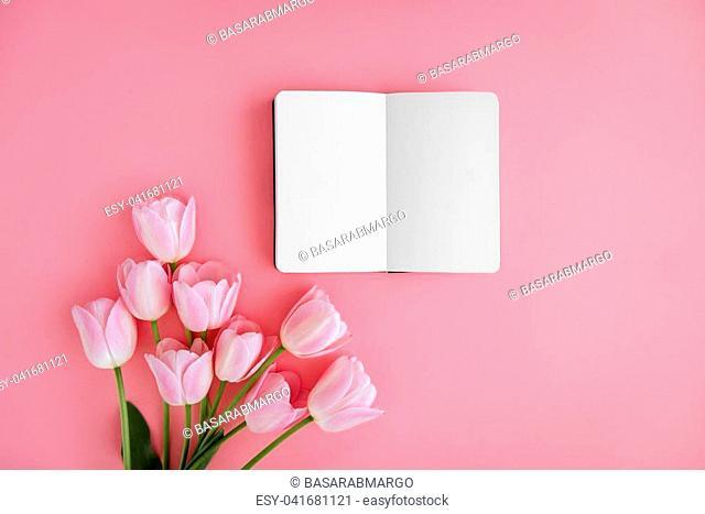 Opened noteboog around beautiful flowers. Pink background. Flat lay style