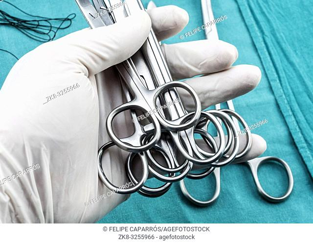 Surgeon working in operating room, hands with gloves holding scissors sutures, conceptual image, composicon horizontal