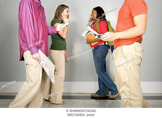 Four students walking along a corridor