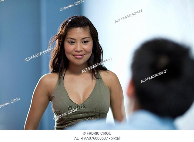 Young woman smiling flirtatiously at man in foreground