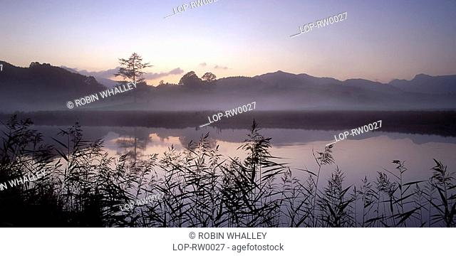 England, Cumbria, Elterwater, Pastel shades and reflections in Elterwater at sunset. The reedy shores of Elterwater are a haven for wildfowl