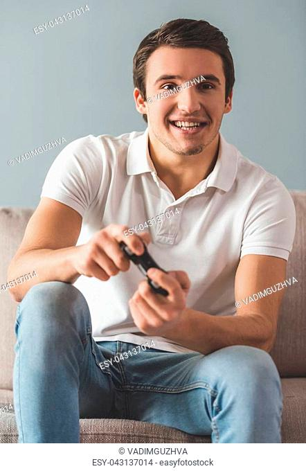 Handsome young man is playing game console and smiling while sitting on couch at home