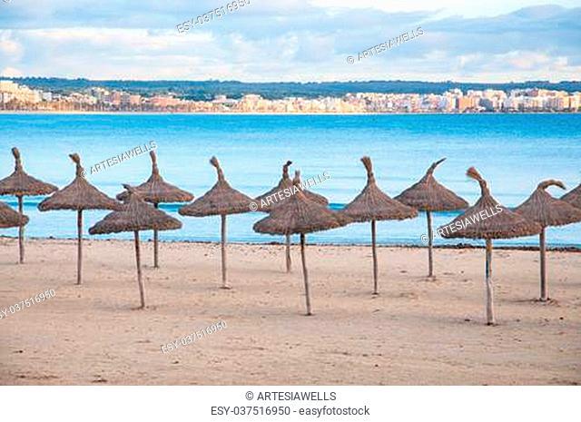 Straw umbrellas on empty beach, Playa de Palma, Majorca