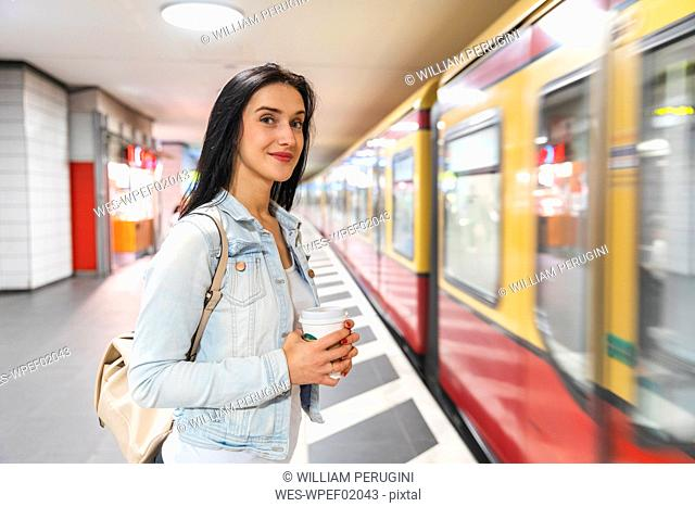 Young woman at metro station waiting for the train, Berlin, Germany