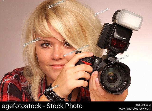 Blond girl taking picture with a DSLR camera