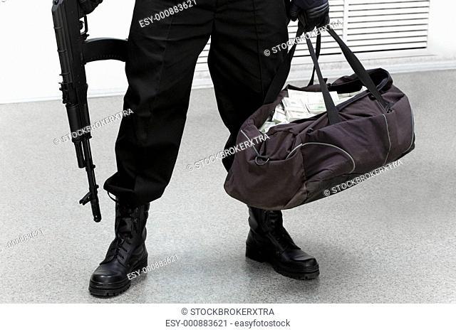 Image of legs of burglar with bag full of stolen money in his hand