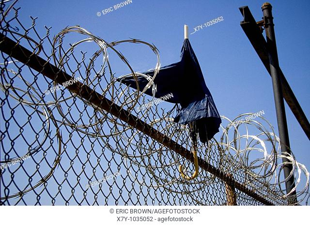 An umbrella stands atop a barbed wire fence