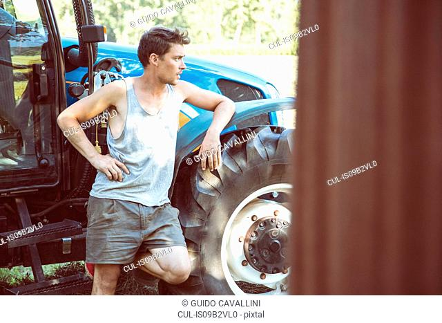 Young male farmworker leaning against tractor