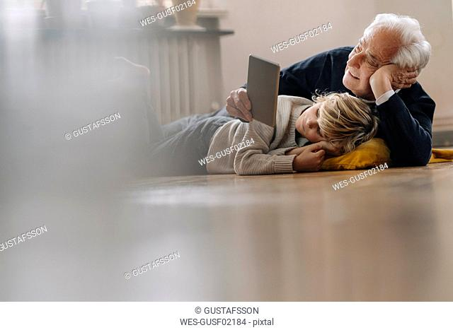 Grandfather and grandson lying on the floor at home using a tablet