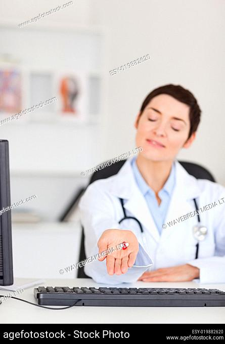 Portrait of a young female doctor showing pills