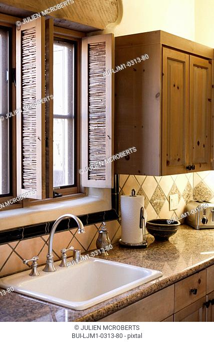 Close-up of a faucet with washbasin and window in the kitchen; Santa Fe; New Mexico; USA