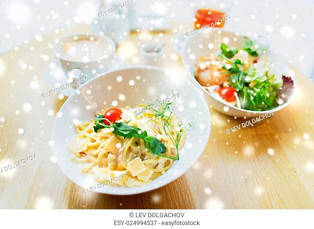 food, cooking and eating concept - close up of pasta in bowl and salad on table at restaurant or home