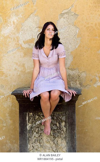 Italy, Florence, Portrait of young woman sitting on pedestal in front of dilapidated wall