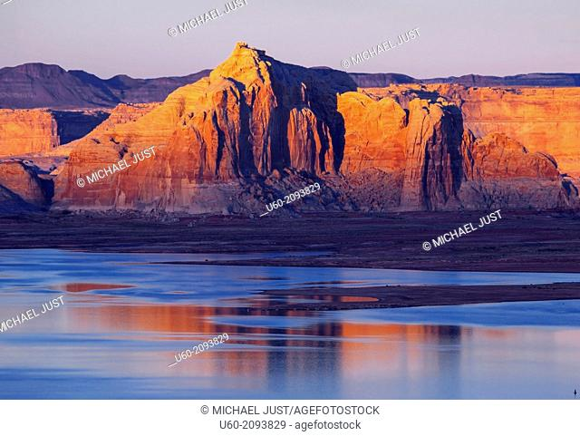The landscape at Lake Powell is reflected in its waters at sunset