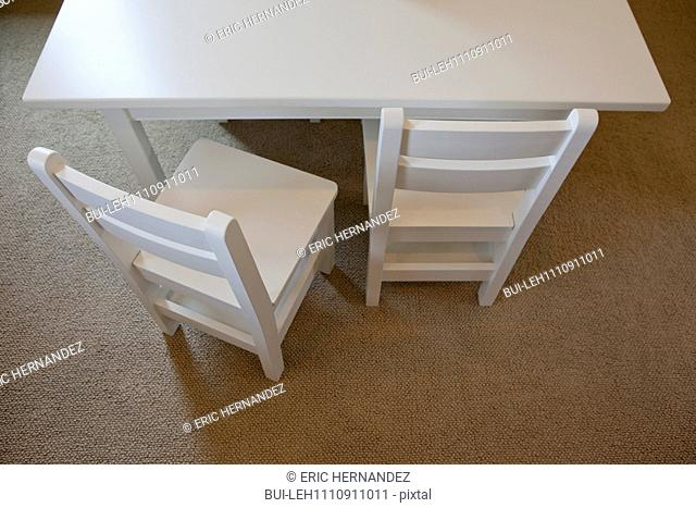 High angle view of two white chairs at cropped table