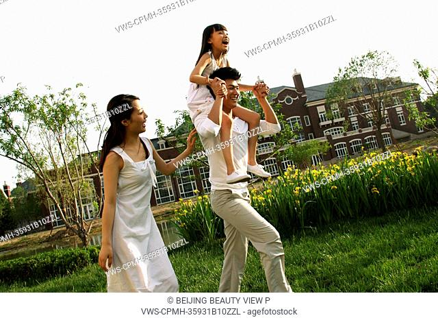 Girl with her parents on grass